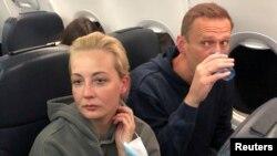 Юлия и Алексей Навални в самолета на път от Берлин за Москва. През август руският опозиционер беше отровен с Новичок на руска територия и излекуван в Германия. Той се върна в страната си на 17 януари и беше арестуван още на летището с аргумента, че е нарушил стара условна присъда, която ще трябва да излежи ефективно.