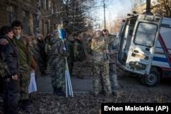 Родственники и члены украинской военно-медицинской части утешают друг друга, оплакивая четырех товарищей, убитых под Дебальцевом в феврале 2015 года.
