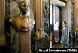 A woman enters Yeliseyevsky past a bust of its founder on April 11, the shop's last day of business.