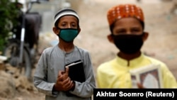 Boys wearing protective masks head to the madrasah in Karachi in July.