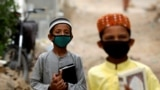 PAKISTAN -- Boys wear protective masks as they head to the madrasa (religious school), during an anti-polio campaign, in a low-income neighborhood as the spread of the coronavirus disease (COVID-19) continues, in Karachi, July 20, 2020