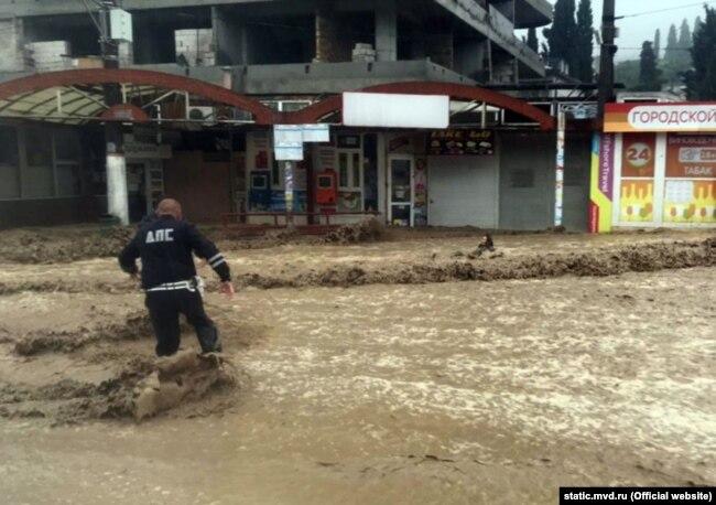 Сотрудник полиции спасает женщину от наводнения в Ялте, 18 июня 2021 года