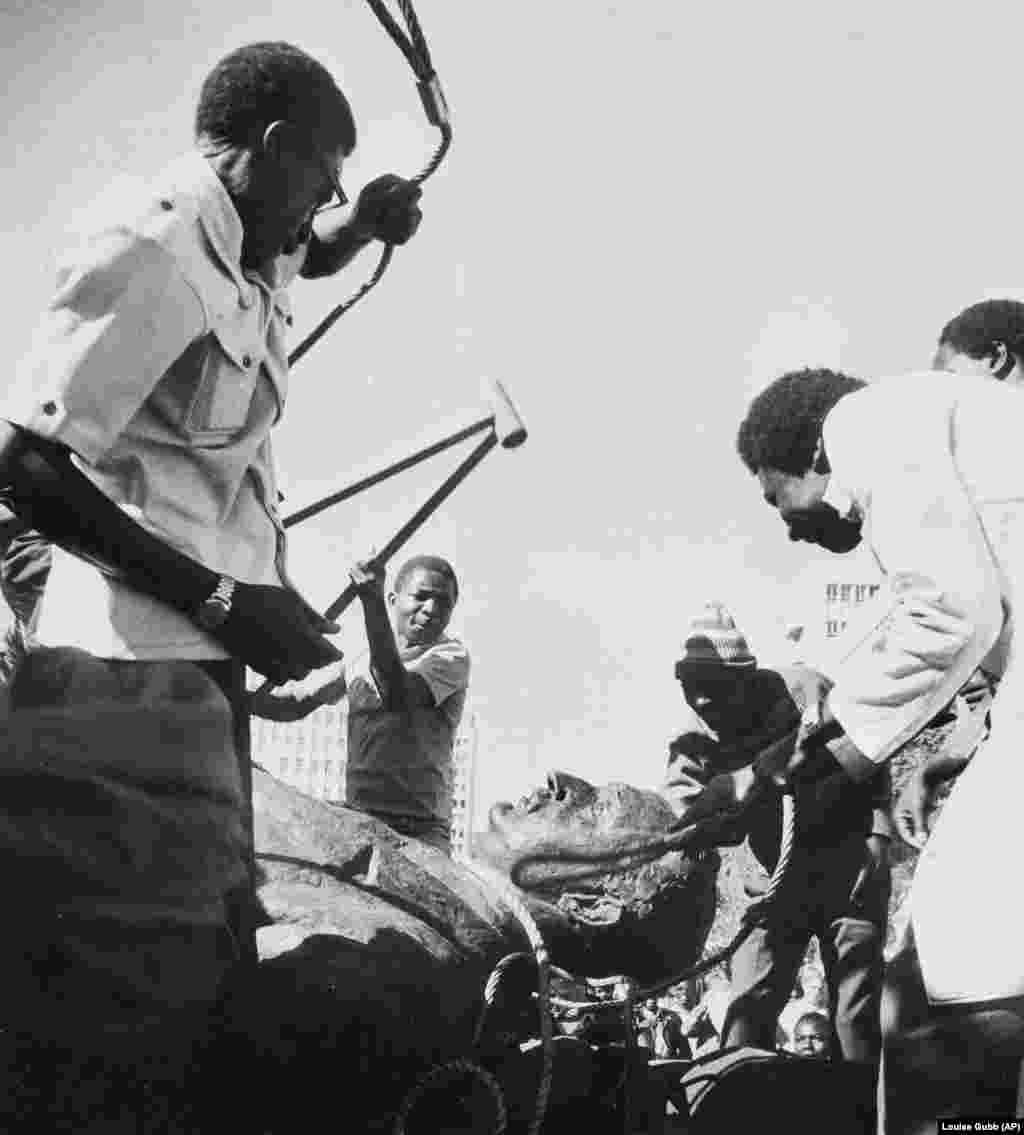 Мужчины избивают статую британского политического деятеля Сесила Родса в Зимбабве после того, как африканская страна, ранее известная как Родезия, получила независимость от Великобритании в 1980 году