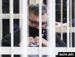 Viktar Babaryka makes a heart symbol while sitting in a cage at a court hearing in Minsk on February 17.