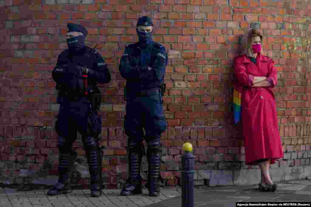 Поліцейські стоять біля жінки, яка тримає сумку кольору веселки. Варшава, 24 жовтня 2020 року
