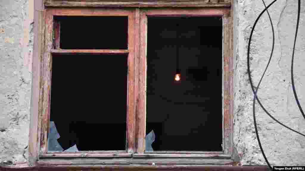 Через разбитое окно видна горящая лампочка