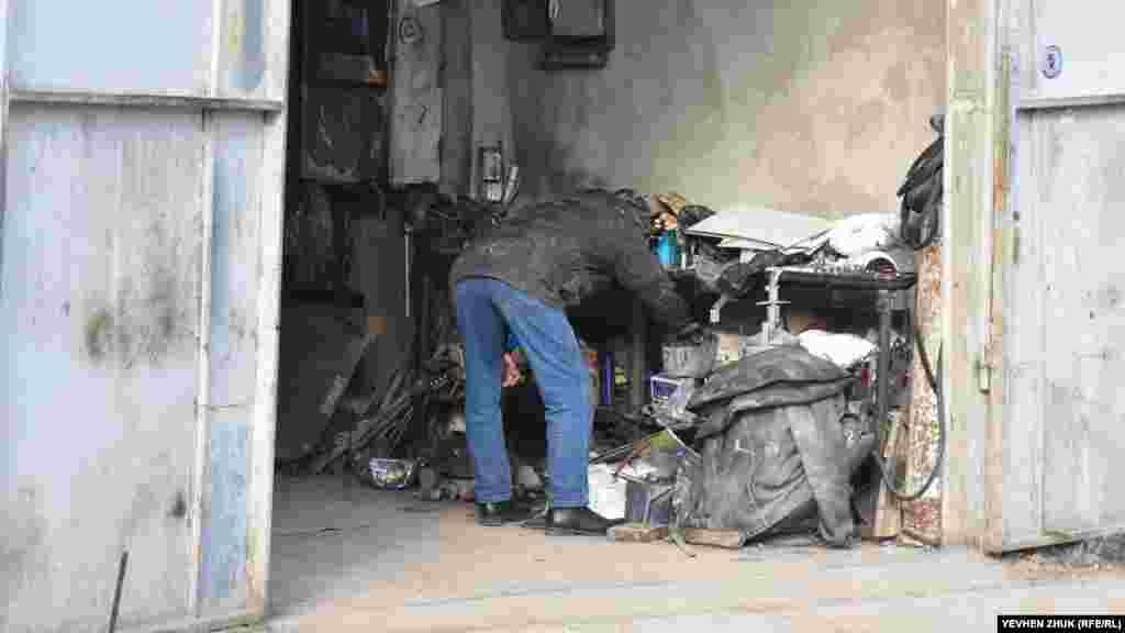 Чоловік працює в особистому гаражі