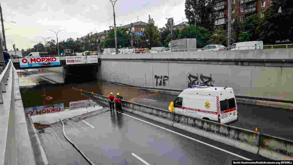 Комунальні служби і ДСНС ліквідовують затоплення проїжджої частини біля станції метро «Дорогожичі» (вулиця Олени Теліги) в Києві, 19 липня 2021 року