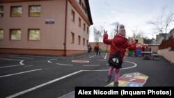 Un copil se joacă la sosirea la școală.