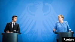 Ukrainian President Volodymyr Zelenskiy (left) and German Chancellor Angela Merkel give statements ahead of talks at the Chancellery in Berlin on July 12.