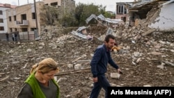 NAGORNO-KARABAKH -- A couple walks in front of a destroyed house after a late October 7th sheling in StepanakertArmenia Insists On Karabakh's 'Right To Self-Determination', October 8, 2020