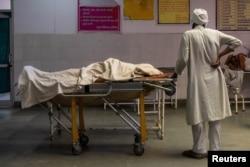 Мужчина с телом умершей от коронавируса супруги. Биджнор, 11 мая