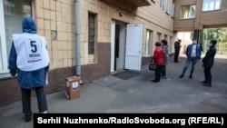 Волонтёр с бюллетенями опроса у входа в избирательный участок