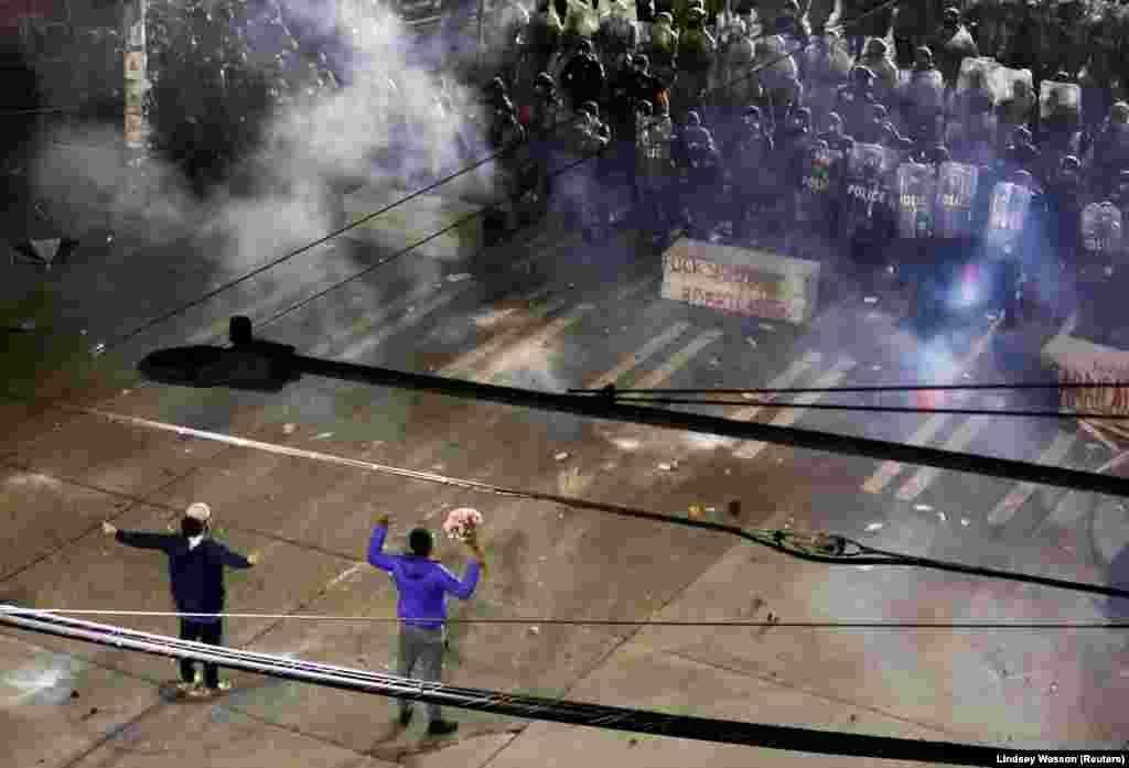 Двоє протестувальників із піднятими руками – навпроти шеренги поліцейських, які готуються застосовувати спецзасоби. Протест через смерть Джорджа Флойда. Штат Вашингтон, США. 8 червня 2020 року