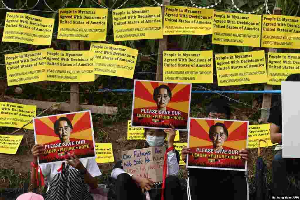 Протестувальники тримають плакати із зображенням затриманої лідерки М'янми Аун Сан Су Чжі і вимагають її звільнення під час демонстрації проти військового перевороту перед посольством США в Янгоні, М'янма, 16 лютого 2021 року