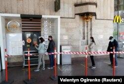 Кияни в захисних масках тримають дистанцію в черзі до ресторану МакДональдс. Київ, 13 травня 2020 року