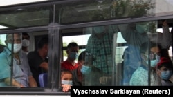 People wearing protective face masks ride a bus in Ashgabat, despite the country officially having had no cases of COVID-19.