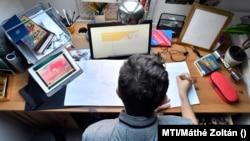 Több táblagépe segítségével készíti el egy középiskolás fiú a történelemből kapott feladatait 2020. március 17-én.