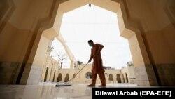 Мужчина моет полы в мечети перед священным месяцем Рамадан во время пандемии коронавируса в Пешаваре. 12 апреля 2021 года.