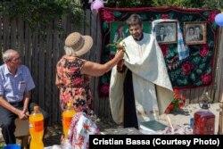 """O femeie dăruiește flori unui preot în timpul ritualului de resfințire a Fântânii lui Florescu, construită de Haralambie, în cadrul zilelor deschise """"Fântânile Sudului""""."""