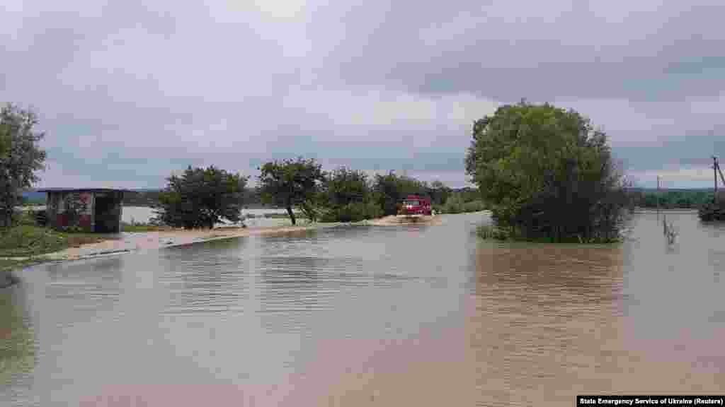 Пожежне авто їде затопленою дорогою біля села Мельнич Жидачівського району на Львівщині, 24 червня