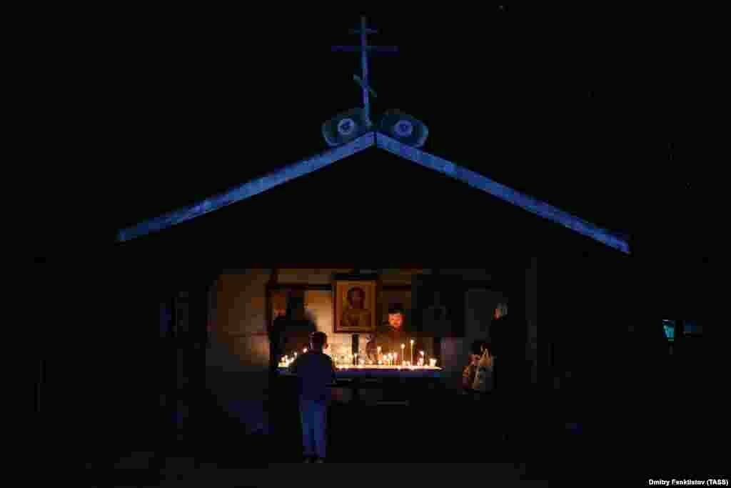 Candles light up a shrine in the village of Velikoretskoye.