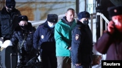 Kremlin critic Aleksei Navalny (in green jacket) is escorted by police officers after a court hearing in Khimki outside Moscow on January 18.
