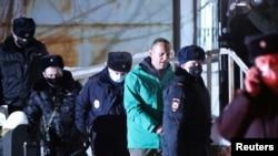 Российского оппозиционера Алексея Навального сопровождают сотрудники полиции после суда, состоявшегося в УВД города Химки. 18 января 2021 года.