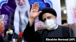 Ebrahim Raisi waves to journalists while registering his candidacy for the upcoming presidential election at the Interior Ministry in Tehran on May 15.