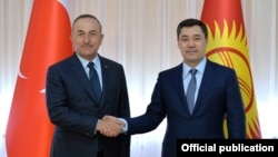 Turkish Foreign Minister Mevlut Cavusoglu (left) shakes hands with Kyrgyz President Sadyr Japarov at their meeting in Bishkek on March 10.