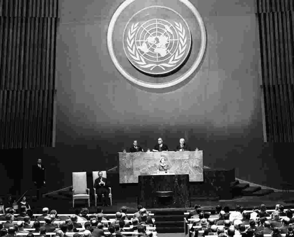 Regina Elisabeta a II-a se adresează sesiunii plenare a Adunării Generale în timpul vizitei sale la Națiunile Unite, New York, pe 21 octombrie 1957. În stânga sa este prințul Philip, iar în spatele ei, sub simbolul ONU, sunt, de la stânga la dreapta: secretarul general Dag Hammarskjold, președintele Adunării Siu Leslie Munro și asistentul secretar general Andrew Cordier. (Foto AP)
