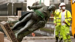 Велика Британія. Працівники знімають статую Роберта Мілігана поруч із музеєм Доклендса в Лондоні, 9 червня 2020 року