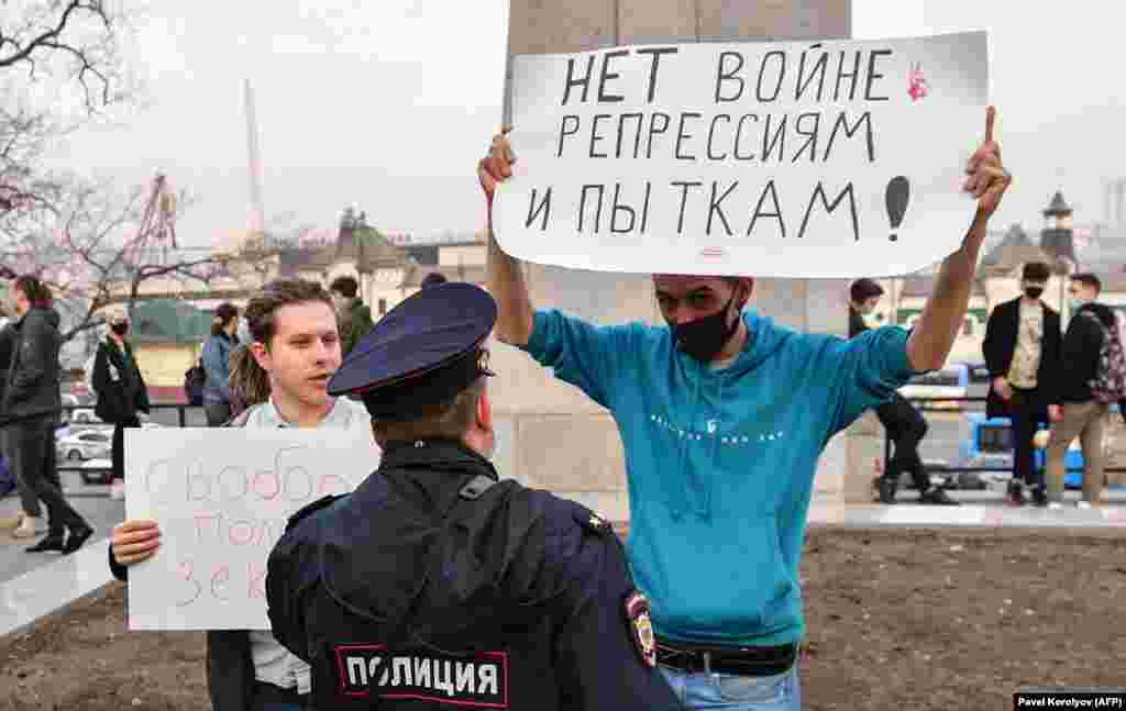 """A police officer speaks with an opposition supporter holding a poster reading """"No war, repression, and torture!"""" at the rally in Vladivostok."""