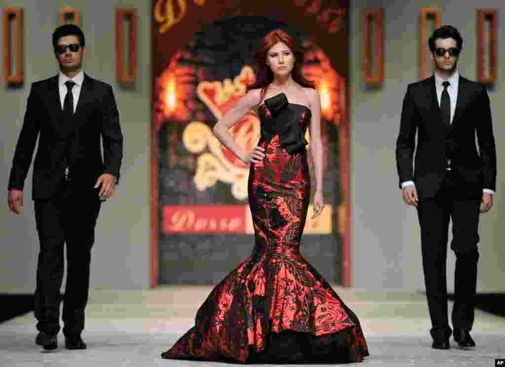 Chapman struts down a Turkish catwalk flanked by two men posing as secret service agents at a fashion show in Antalya on June 8, 2012.