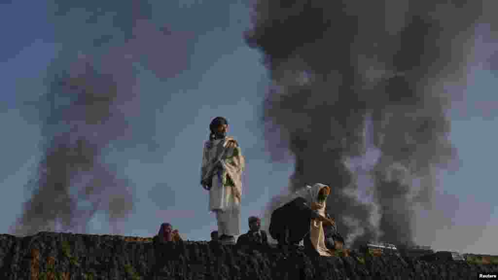 Smoke rises past residents standing on the wall of a truck terminal where NATO fuel tankers were set ablaze in Quetta in December.