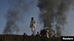 Smoke rises past residents standing on the wall of a truck terminal where NATO fuel tankers were set ablaze in Quetta on December 9.