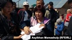 Жители поселка Коксай Карасайского района Алматинской области, протестующие против сноса домов, показывают письменные обращения, ранее направленные в районный акимат и прокуратуру.