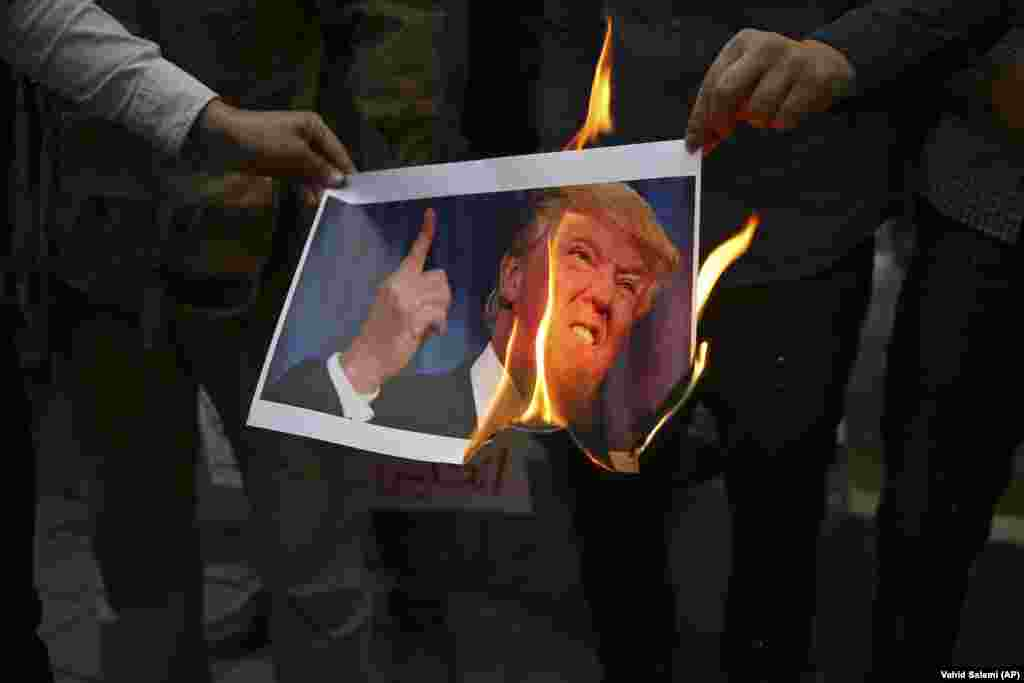 Iranian demonstrators burn a picture of U.S. President Donald Trump during during a protest in front of the former U.S. Embassy in response to Trump's decision to pull out of the nuclear deal and renew sanctions. (AP/Vahid Salemi)