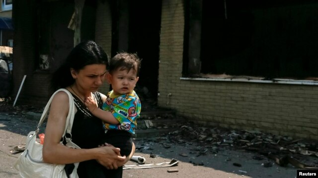 A woman carries a baby as she passes destroyed houses following what locals say was overnight shelling by Ukrainian forces in the eastern town of Slovyansk on June 9.