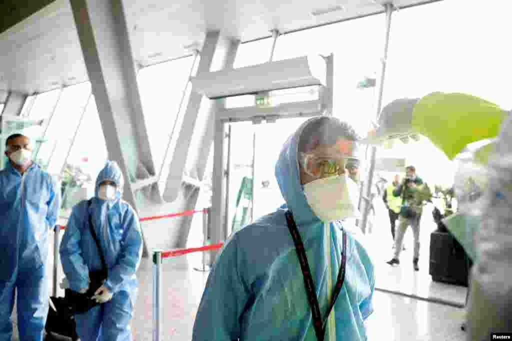 """Сотрудники """"Албанских авиалиний"""" в защитных костюмах проверяют температуру по прилету в Тирану, Албания.1 апреля 2020 года"""