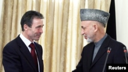 NATO Secretary-General Anders Fogh Rasmussen (left) shakes hands with Afghan President Hamid Karzai during a meeting at the presidential palace in Kabul last year.