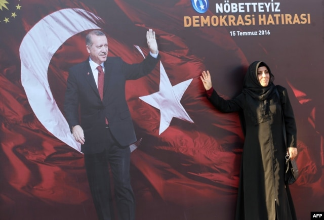 Женщина позирует для фото на фоне плаката с изображением Реджепа Эрдогана. Анкара, 2 августа 2016 года