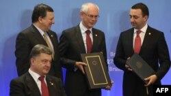 Президент Украины Петр Порошенко (на переднем плане), президент Еврокомиссии Жозе Мануэль Баррозу, президент Европейского совета Херман Ван Ромпей и премьер-министр Грузии Ираклий Гарибашвили на саммите Евросоюза. Брюссель, 27 июня 2014 года.