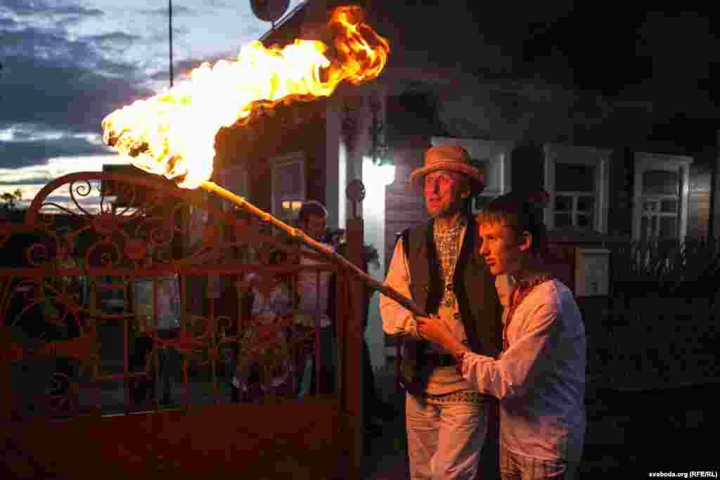 Алесь Пушкін разам з сынам Міколам нясуць паходню, якою запаляць купальскае вогнішча