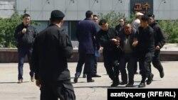Полиция жасағы Тәуелсіздік ескерткіші жанында ұсталған адамды полиция көлігіне апара жатыр. Алматы, 7 мамыр 2016 жыл.