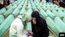 Bosnian Muslim women mourn over a casket during the funeral of 465 Bosnian Muslims at the Potocari Memorial Center in 2007.