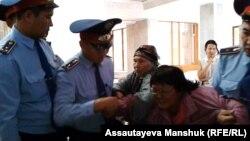 Полицейские производят задержание активиста движения пенсионеров Алматы Райхан Амирбековой в фойе городского акимата. Алматы, 4 октября 2013 года.