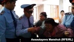 Полицейские задерживают активистку группы алматинских пенсионеров Райхангуль Амирбекову в здании акимата города. Алматы, 4 октября 2013 года.