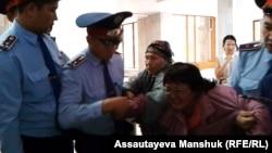 Алматы әкімдігіне барған зейнеткер Райхан Әмірбекованы полиция ұстап алып бара жатыр. 4 қазан 2013 жыл.