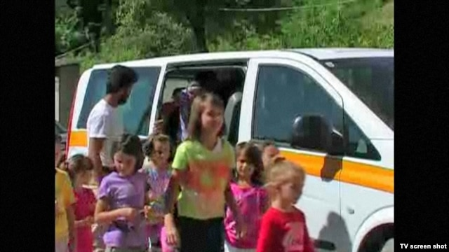 "Schoolchildren from Liplje, Bosnia climb out of a minivan donated by a Dutch NGO to help them get to school. Screen shot from RFE/RL's ""TV Liberty"" program, 24Jul2012."